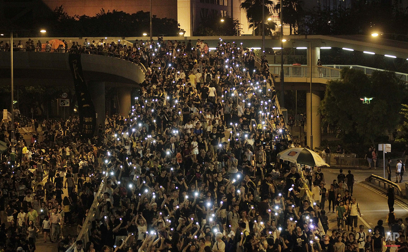 Tens of thousands of pro-democracy demonstrators, some waving lights from mobile phones,  fill the streets in the main finical district of Hong Kong, Wednesday, Oct. 1, 2014. Student leaders of pro-democracy protests in Hong Kong warned Wednesday that if the territory's leader doesn't resign by the end of Thursday they will step up their actions, including occupying several important government buildings. (AP Photo/Wally Santana)