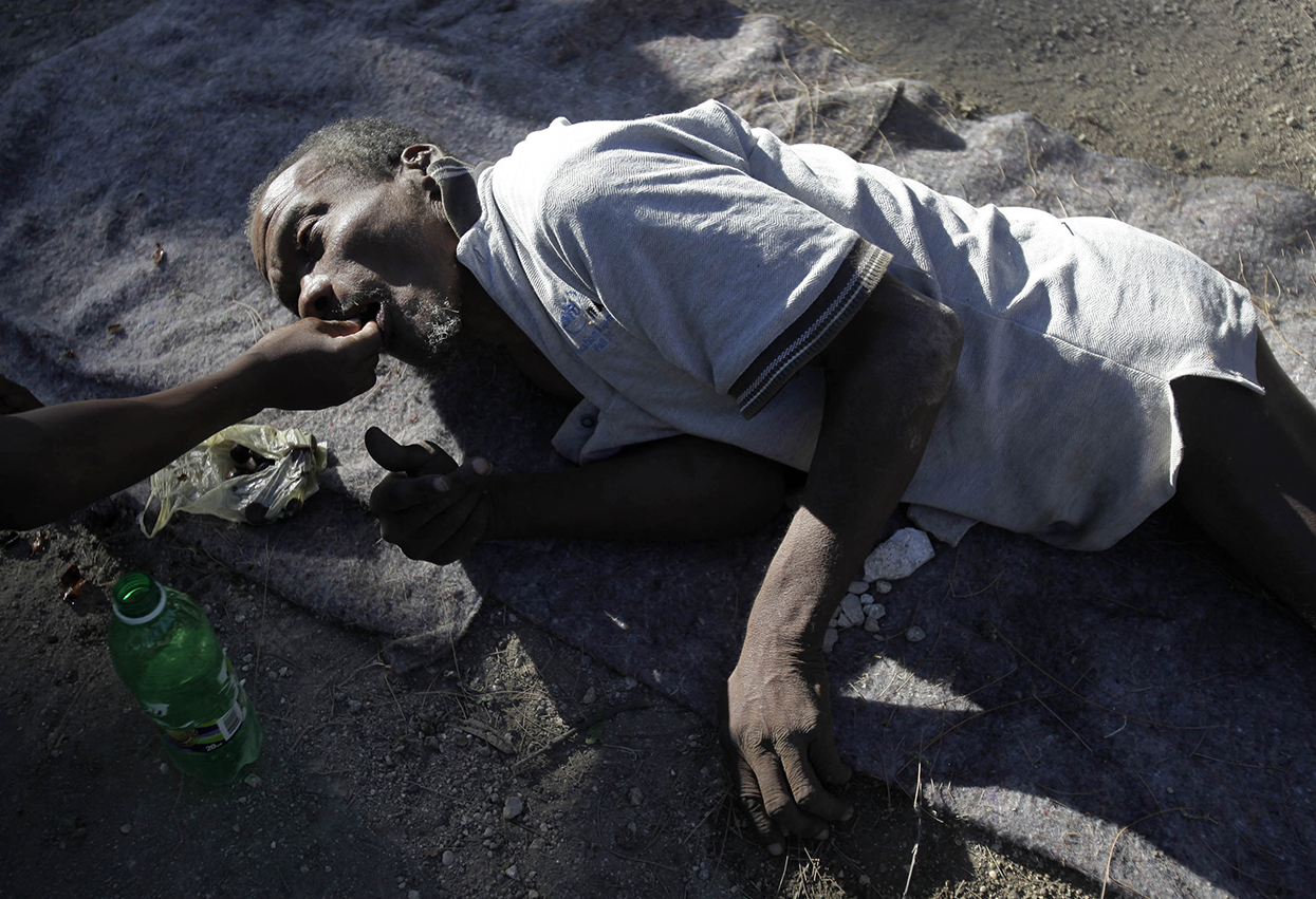 An old man is fed a few nuts from his nephew while lying outside his quake damaged nursing home in Port-au-Prince, Sunday, Jan. 17, 2010.  More than 100 old men and women were living outside the home, that was damaged during Tuesday's earthquake, with no food or care other than an occasional bath from two medical orderlies who remained to help. (AP Photo/Julie Jacobson)