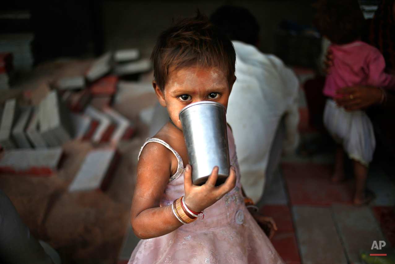 A small girl drinks water from a steel glass as her parents construct a pavement in New Delhi, India, Wednesday, May 8, 2013. The capital is reeling under a heat wave with temperatures touching 40.8 degrees Celsius (105 degrees Fahrenheit) Tuesday, two degrees above normal for this time of the year. (AP Photo/Saurabh Das)