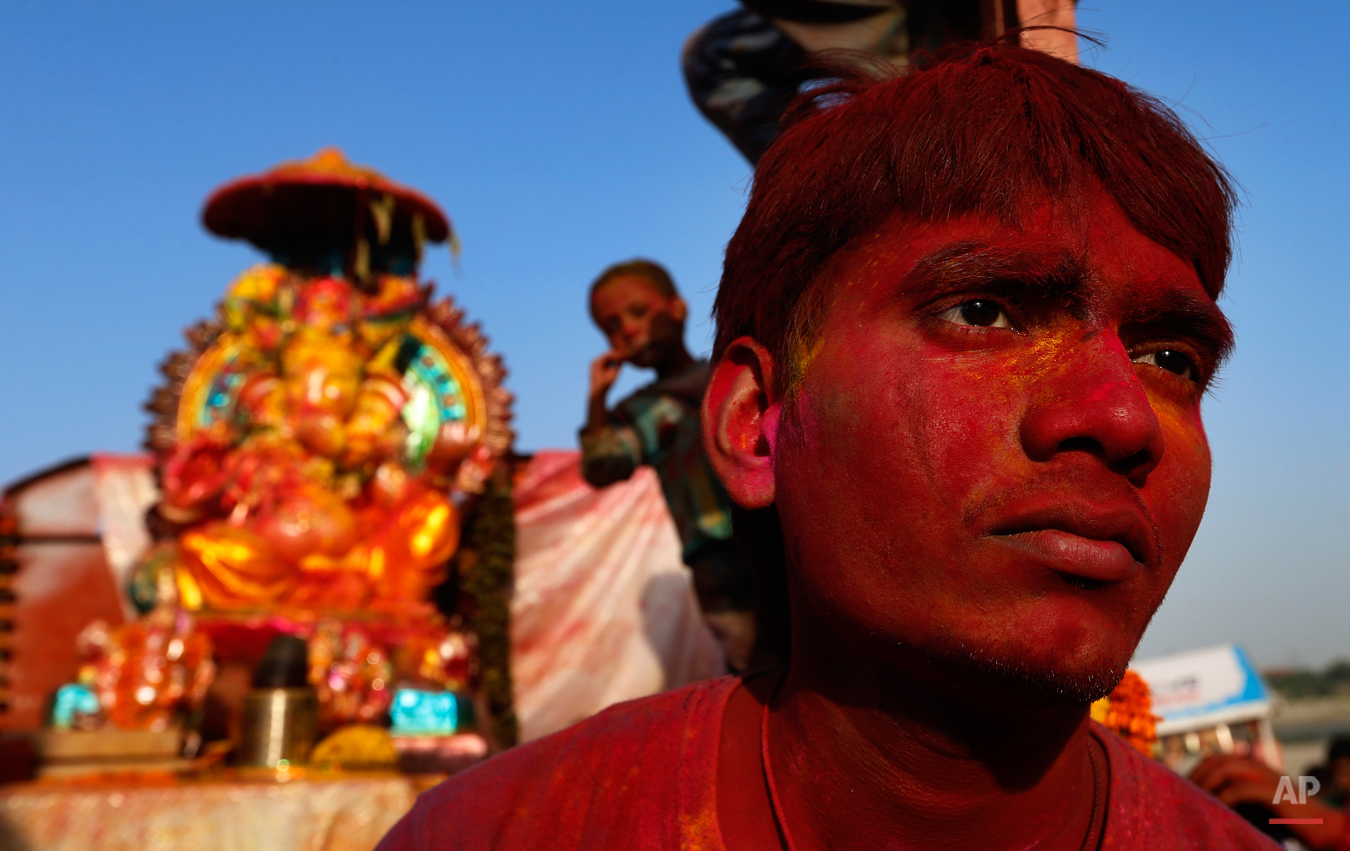 An Indian man sits with a statue of elephant headed Hindu God Ganesha before its immersion into the River Yamuna in New Delhi, India, Wednesday, Sept. 18, 2013. The immersion marks the end of the ten-day long Ganesh Chaturthi festival that celebrates the birth of the Hindu God of wisdom, prosperity and good fortune. (AP Photo/Saurabh Das)