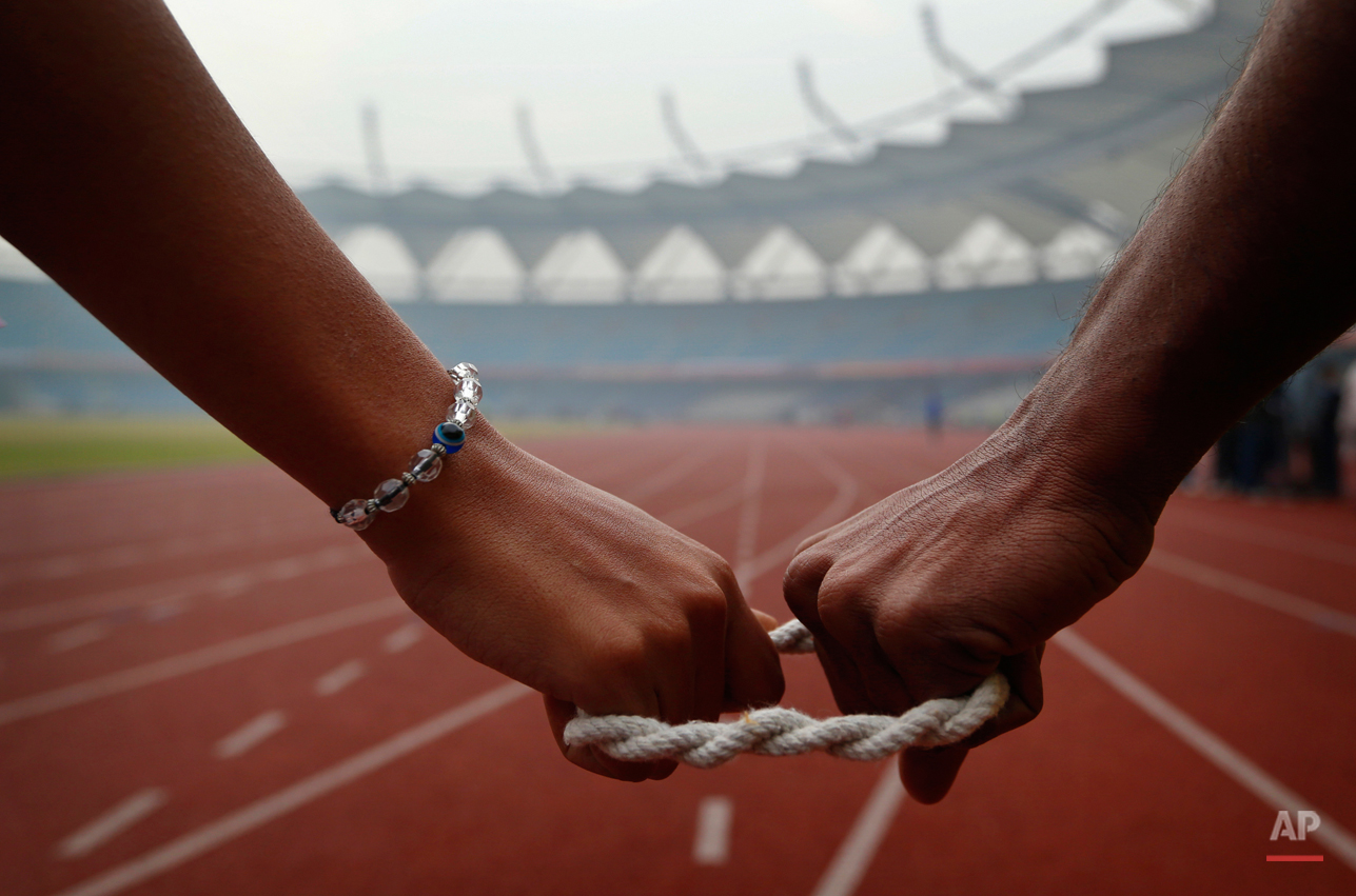 In this Tuesday, Dec. 11, 2012 photo, a blind athlete, left, is connected to her guide as she gets ready to run during the 18th National Sports Meet for the Blind in New Delhi, India. The four day event ends Friday. (AP Photo/Saurabh Das)
