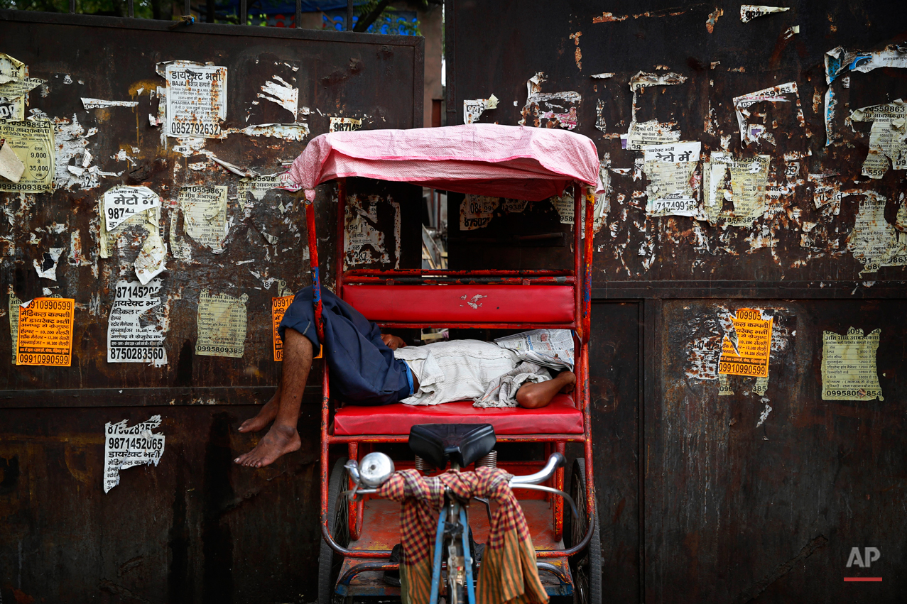 A rickshaw puller covers his face with a newspaper as he takes a nap in a hot summer afternoon in New Delhi, India, Friday, May 2, 2014. Daytime temperatures touched 42 degrees Celsius (108 degrees Fahrenheit). (AP Photo/Saurabh Das)