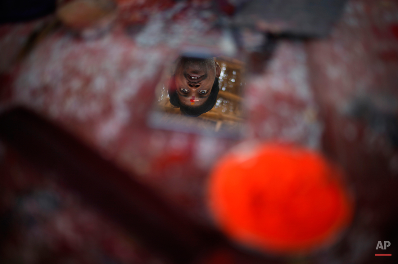A comb and a bowl of vermillion powder lie on a shelf as a Hindu holy man is reflected in a mirror kept for the use of devotees after bathing, near Sangam, confluence of Hindu holy rivers of Ganges, Yamuna and the mythical Saraswati, at the Maha Kumbh festival in Allahabad, India, Thursday, Feb. 14, 2013. Millions of Hindu pilgrims are attending the Maha Kumbh festival, which is one of the world's largest religious gatherings that lasts 55 days and falls every 12 years. During the festival pilgrims bathe in the holy Ganges River in a ritual they believe can wash away their sins. (AP Photo/ Saurabh Das)