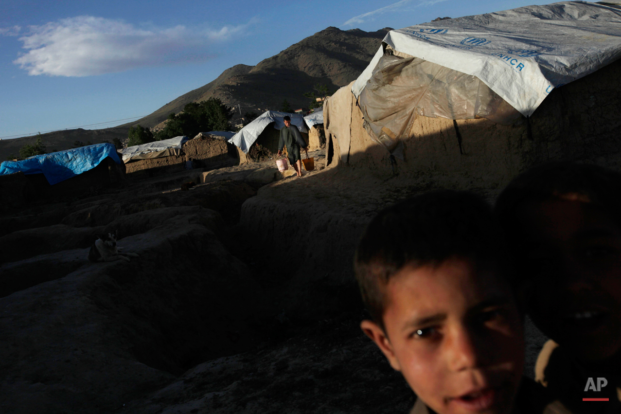 An internally displaced man carries water to his hut as a small boy looks on at a camp for the internally displaced in Kabul, Afghanistan, Thursday, May 13, 2010. (AP Photo/Saurabh Das)