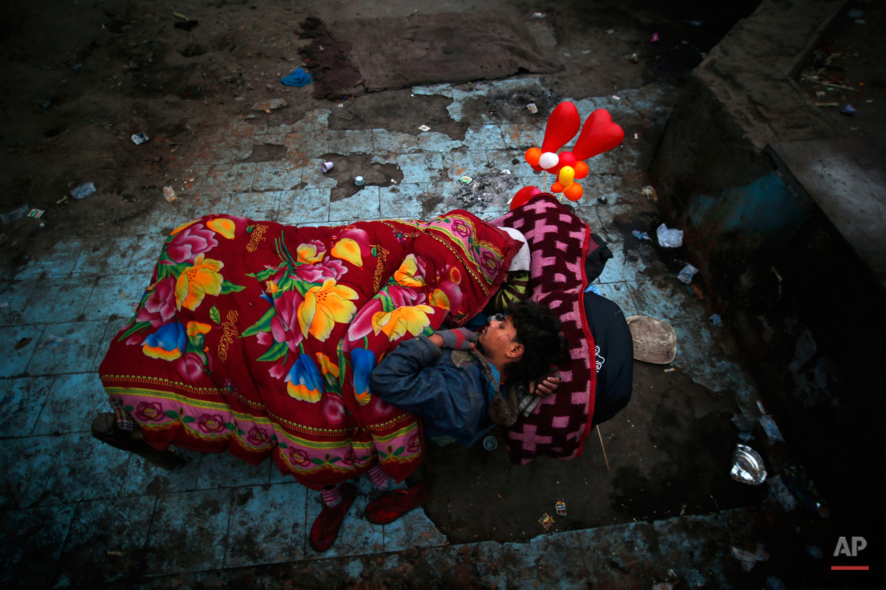 A homeless man and his wife, white scarf covering her head, share a rented bed as balloons inflated in the shape of hearts adorn their cot at a poor neighborhood in New Delhi, India, Wednesday, Jan. 15, 2014. Beds on a cot with blankets cost approximately $.50 while a bed on the ground with blankets cost $.15 per day. (AP Photo/Saurabh Das)