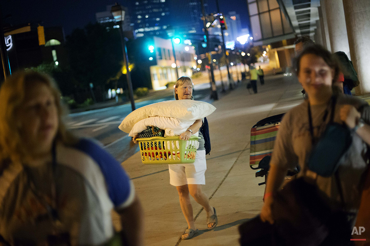 Jodi Huizenga, of Fort Lauderdale, Fla., carries out her belongings after a sleepover in the College Football Hall of Fame, Thursday, Aug. 14, 2014, in Atlanta. The hall was previously located in South Bend, Ind., but was plagued by poor attendance. Five years ago, the National Football Foundation announced a deal to move it to Atlanta, on a site near the Georgia Dome and overlooking Centennial Olympic Park. (AP Photo/David Goldman)