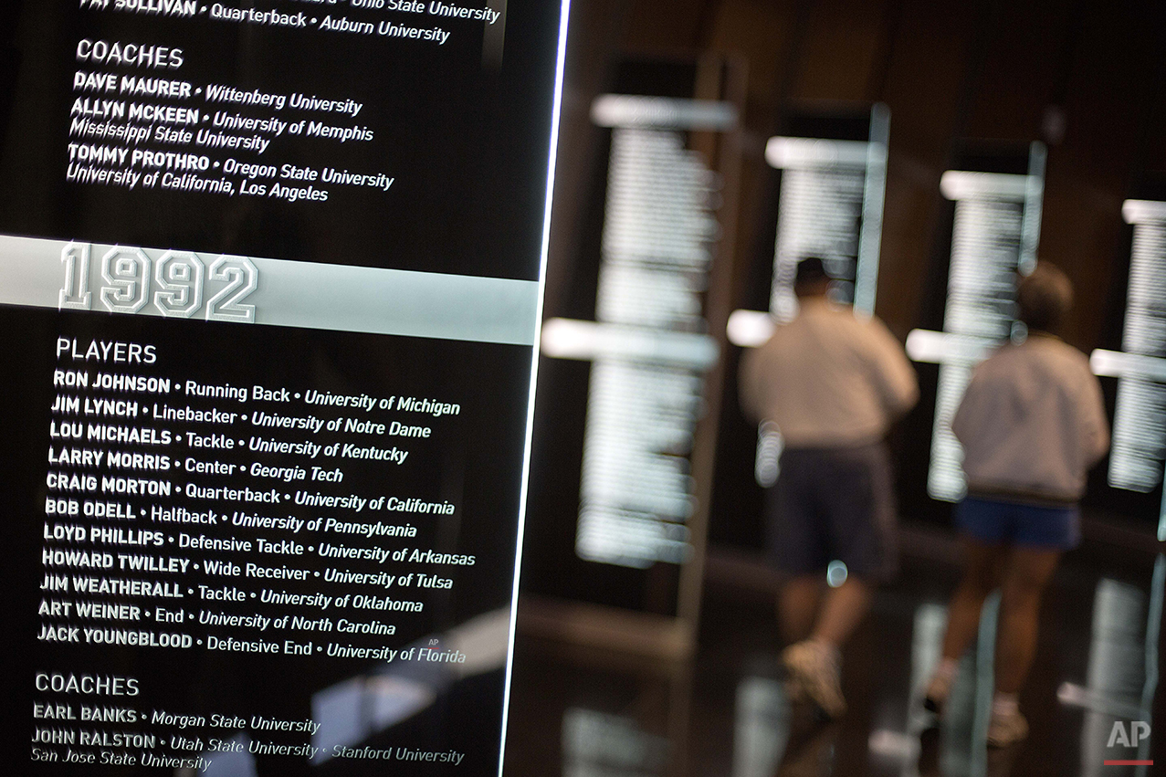 Names of inductees from 1992 are displayed as guests tour the College Football Hall of Fame, Wednesday, Aug. 13, 2014, in Atlanta. Visitors can use touch screens to access individual profiles of more than 1,100 players and coaches that are enshrined in the Hall. (AP Photo/David Goldman)