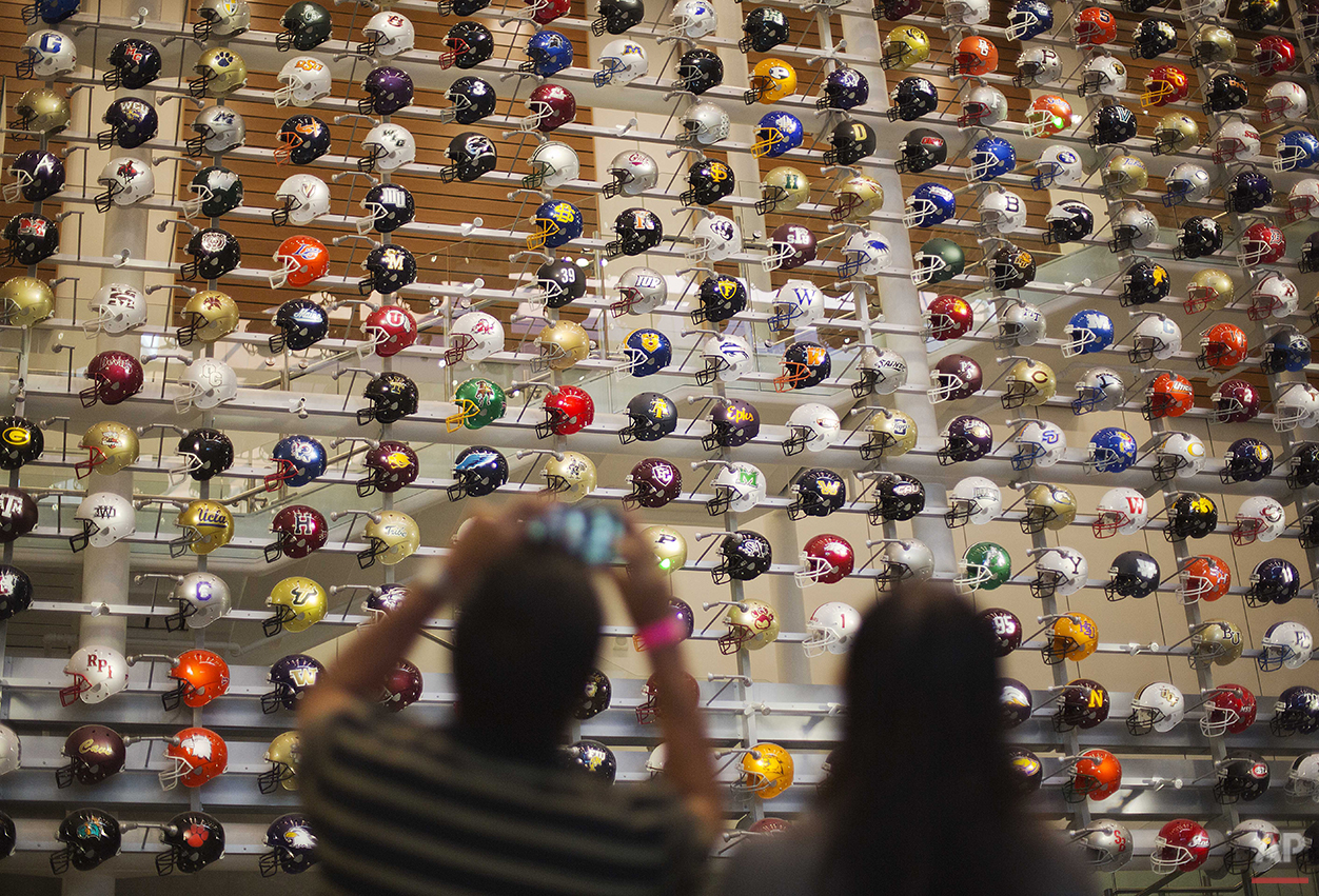 Helmets representing the 768 college football programs in the U.S. are displayed as fans arrive to spend the night in the College Football Hall of Fame, Wednesday, Aug. 13, 2014, in Atlanta. The school associated with a fan's registration card will light up their team's helmet upon swiping the card at the entry to the museum. (AP Photo/David Goldman)