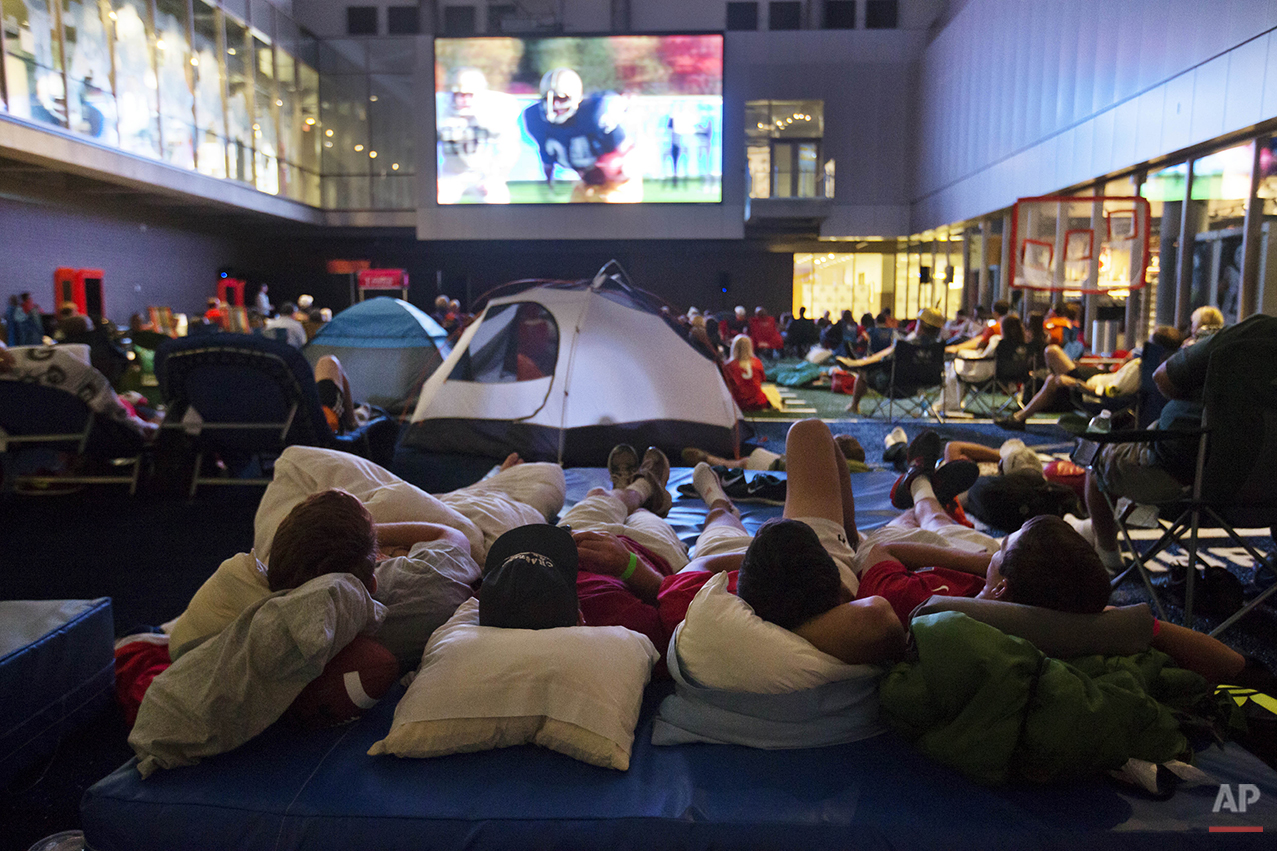 """From left, Danny Mason, Walker Tuten, Nick Toomey and Matt Filer, watch the movie """"Rudy"""" during a sleepover in the College Football Hall of Fame, Wednesday, Aug. 13, 2014, in Atlanta. The crowd fell asleep to the playing of college football themed movies such as """"Rudy"""" and """"We are Marshall"""" on the jumbotron.  (AP Photo/David Goldman)"""