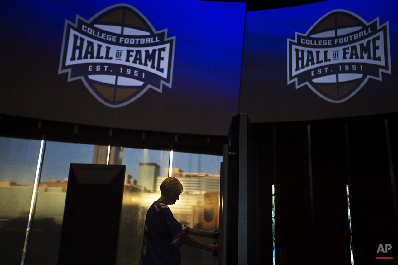 Valerie Herriman, of Augusta, Ga., tours the College Football Hall of Fame before spending the night there as the sun sets against the downtown skyline in the background, Wednesday, Aug. 13, 2014, in Atlanta. One hundred contest winners who wrote an essay detailing their love of college football were selected to stay with a guest overnight in Atlanta's College Football Hall of Fame before its grand opening and win a year's supply of Chick-fil-A. (AP Photo/David Goldman)