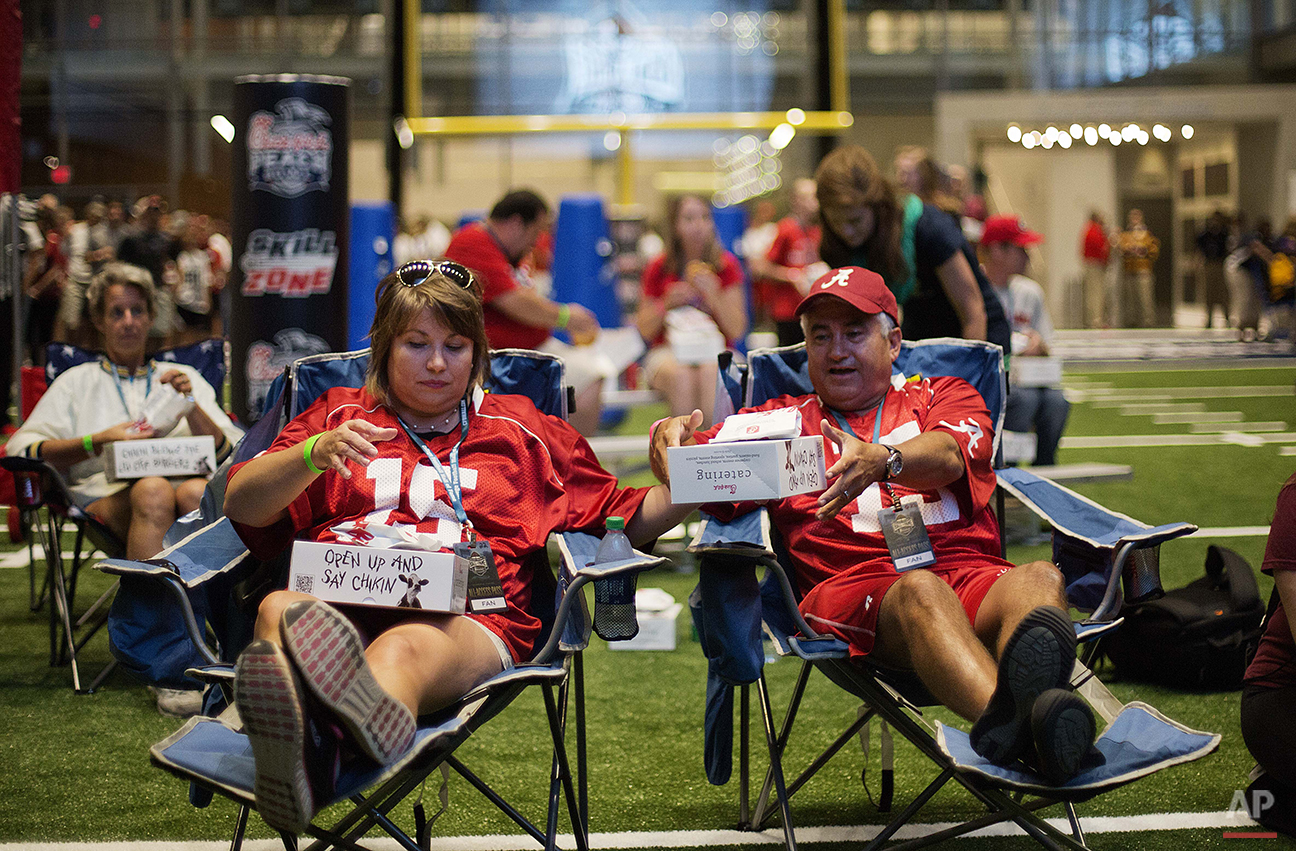 """Amy, left, and Louis Valenzuela, of Marietta, Ga., sit down to eat dinner on the turf as part of a sleepover in the College Football Hall of Fame, Wednesday, Aug. 13, 2014, in Atlanta. """"It's awesome,"""" said Amy, an Alabama fan. """"I think I already pulled my back but it's so much fun."""" (AP Photo/David Goldman)"""
