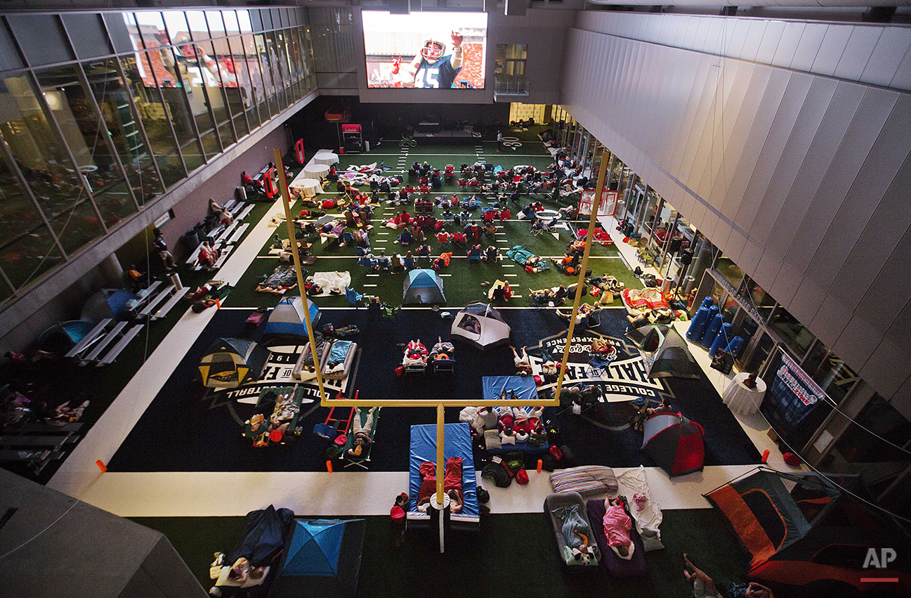 """Guests watch from the turf as the movie """"Rudy"""" is plays during a sleepover in the College Football Hall of Fame in the early hours, Thursday, Aug. 14, 2014, in Atlanta. The crowd of 200 who came from as far away as Hawaii were among the first to experience the College Football Hall of Fame and Chick-fil-A Fan experience before it opened to the public on Aug. 23. (AP Photo/David Goldman)"""