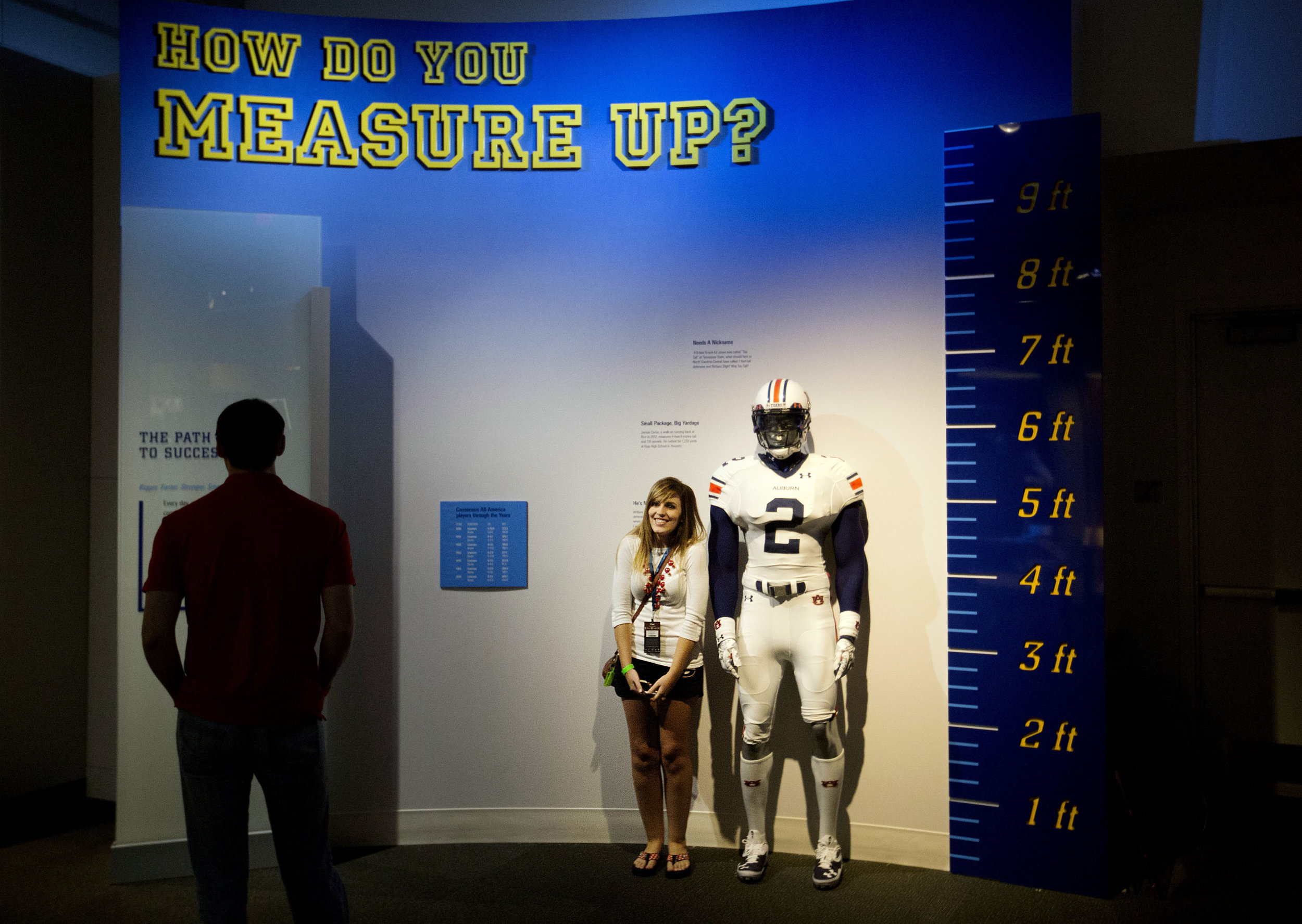 """Joanna Jinright, of Dalton, Ga., right, measures herself next to a mannequin of a football player as Anders Ravenholt, of Chattanooga, Tenn., left, looks on during a tour of the College Football Hall of Fame, Wednesday, Aug. 13, 2014, in Atlanta. One hundred contest winners who wrote an essay detailing their love of college football were selected to stay with a guest overnight in Atlanta's College Football Hall of Fame before its grand opening and win a year's supply of Chick-fil-A. The crowd of 200 who came from as far away as Hawaii were among the first to experience the College Football Hall of Fame and Chick-fil-A Fan experience before it opens to the public on Aug. 23. After touring the exhibits guest were served dinner on the football field before pitching their tents on the turf and settling in for the night as college football themed movies such as """"Rudy""""were played on the jumbotron. The hall was previously located in South Bend, Indiana, but was plagued by poor attendance. (AP Photo/David Goldman)"""