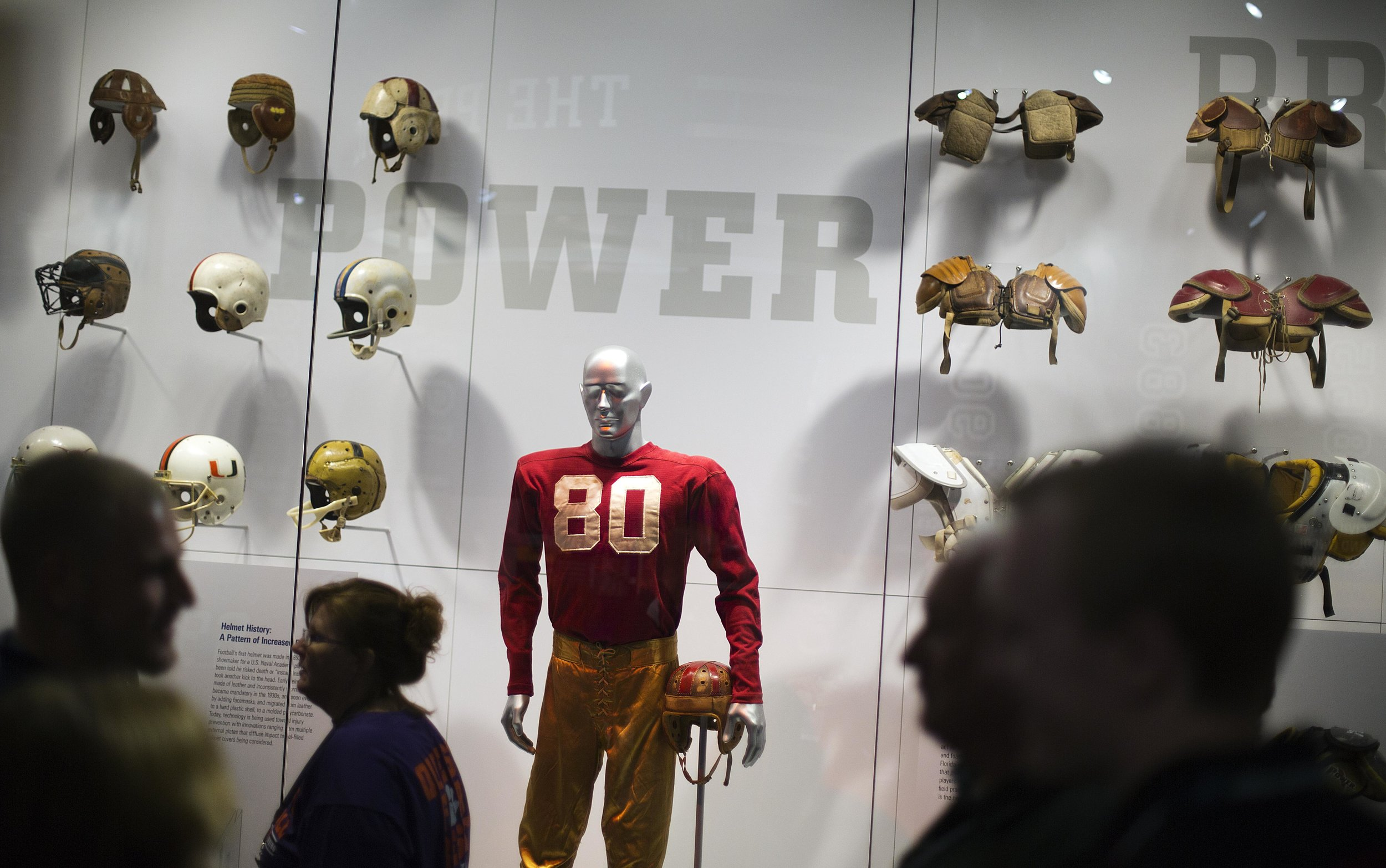 """An exhibit displaying the evolution of protective equipment is viewed by visitors during a tour at the College Football Hall of Fame, Wednesday, Aug. 13, 2014, in Atlanta. One hundred contest winners who wrote an essay detailing their love of college football were selected to stay with a guest overnight in Atlanta's College Football Hall of Fame before its grand opening and win a year's supply of Chick-fil-A. The crowd of 200 who came from as far away as Hawaii were among the first to experience the College Football Hall of Fame and Chick-fil-A Fan experience before it opens to the public on Aug. 23. After touring the exhibits guest were served dinner on the football field before pitching their tents on the turf and settling in for the night as college football themed movies such as """"Rudy""""were played on the jumbotron. The hall was previously located in South Bend, Indiana, but was plagued by poor attendance. (AP Photo/David Goldman)"""