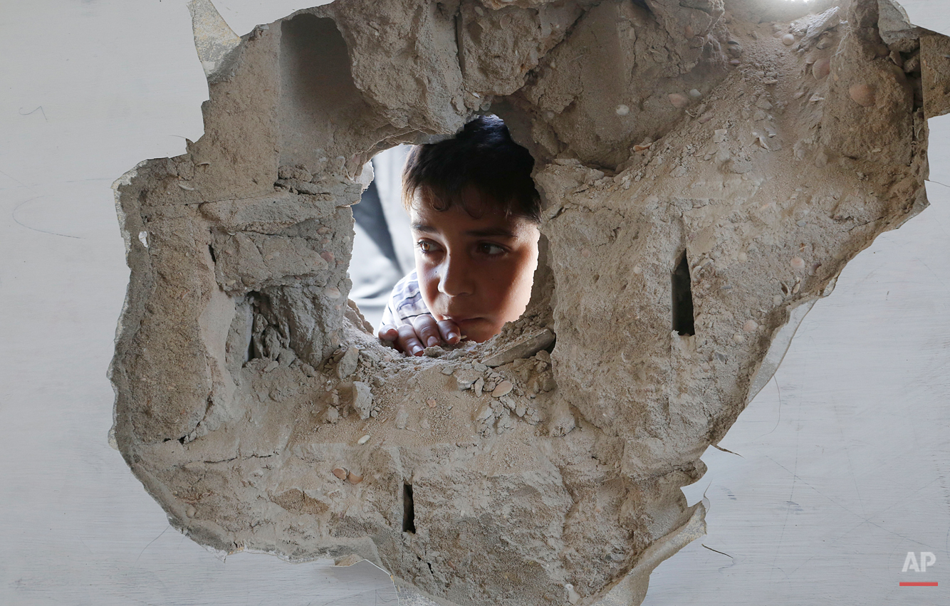 A boy looks through a hole on the wall made after an Israel strike at the Abu Hussein U.N. school in the Jebaliya refugee camp in the northern Gaza Strip on Wednesday, July 30, 2014. Israeli tank shells slammed into a crowded U.N. school Wednesday sheltering Gazans displaced by fighting, killing more than a dozen and wounding tens after tearing through the walls of two classrooms, a spokesman for a U.N. aid agency and a health official said. The Israeli military said mortar shells had been fired from near the school, and that soldiers fired back. (AP Photo/Hatem Moussa)
