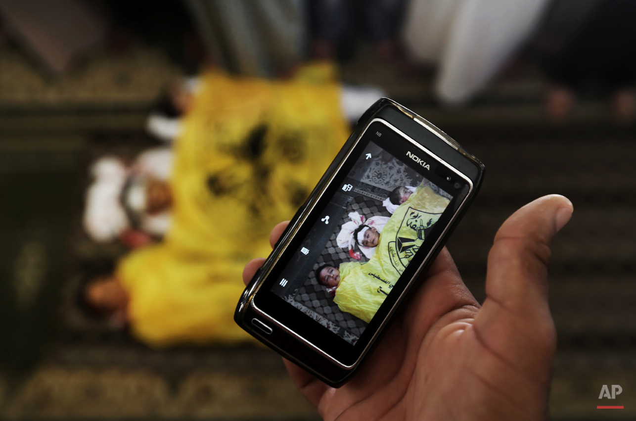 A man takes a photo with his mobile phone of the lifeless bodies of Qasim Alwan, 4, Imad Alwan, 6, and Rizk Hayek, 1, who were killed Friday by an Israeli tank shell, during their funeral in Gaza City, Saturday, July 19, 2014. Relatives say the tank shell kit the Alwan family's kitchen, killing Qasim and Imad. Hayek, who lived nearby, was killed by shrapnel. (AP Photo/Hatem Moussa)