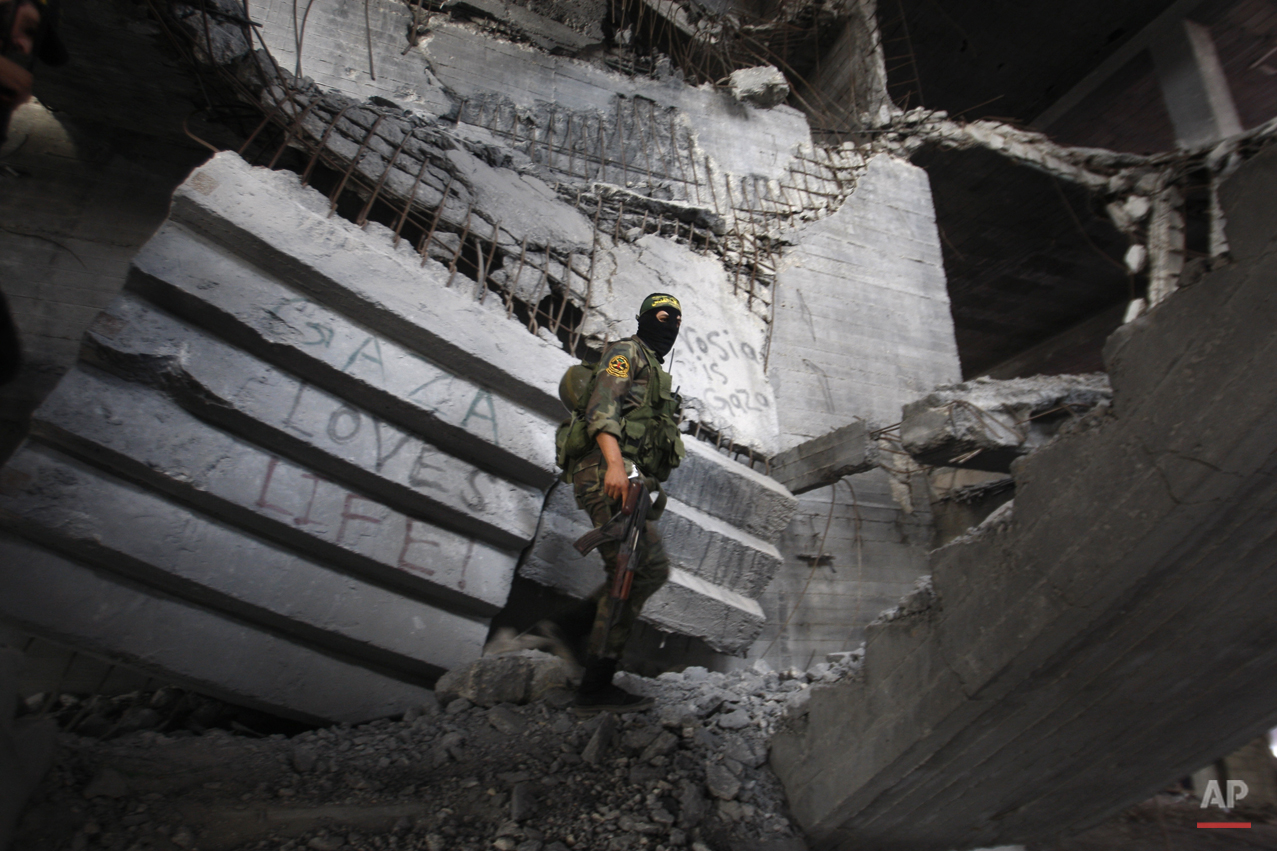 An Islamic Jihad militant walks through a destroyed building adjacent to a rally marking the 25th anniversary of the movement in Gaza City, Thursday, Oct. 4, 2012. (AP Photo/Hatem Moussa)