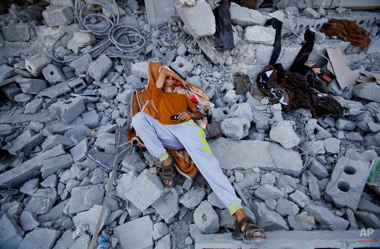 A Palestinian sleeps on the rubble of his home in Beit Hanoun, Gaza Strip, Monday, Aug. 11, 2014. An Egyptian-brokered cease-fire halting the Gaza war held into Monday morning, allowing Palestinians to leave homes and shelters as negotiators agreed to resume talks in Cairo. (AP Photo/Hatem Moussa)