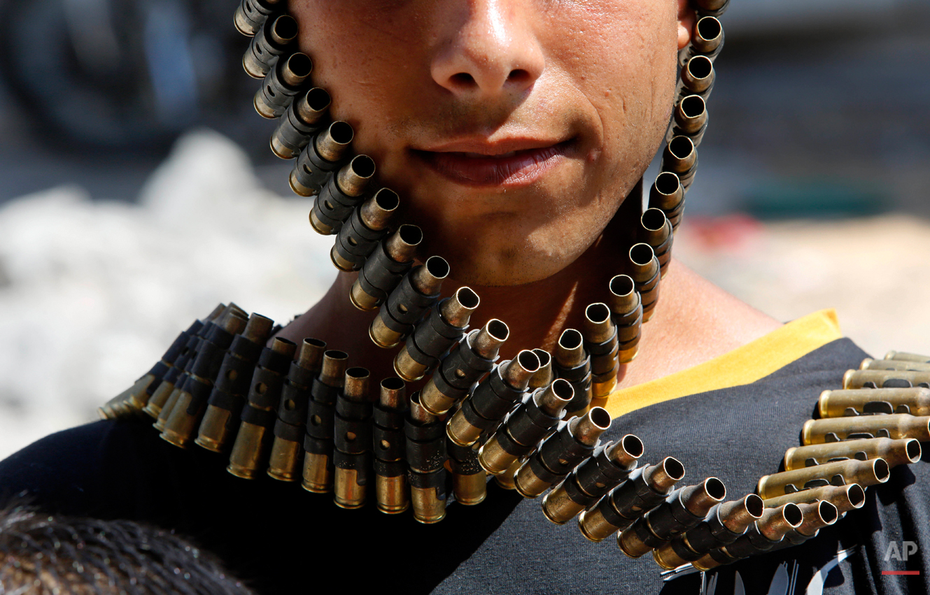 A Palestinian youth wraps a bandolier of spent bullets leftover by the Israeli army, next to his destroyed home in Beit Hanoun, Gaza Strip, Monday, Aug. 11, 2014. An Egyptian-brokered cease-fire halting the Gaza war held into Monday morning, allowing Palestinians to leave homes and shelters as negotiators agreed to resume talks in Cairo. (AP Photo/Hatem Moussa)
