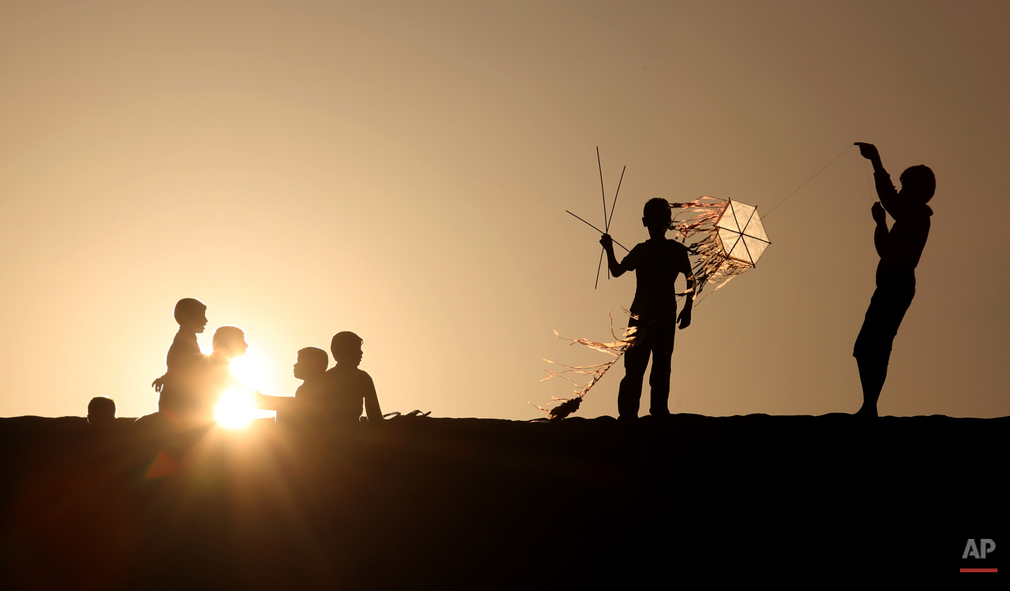 Palestinian children fly kites and sit watching the sunset n Khan Younis, a town and refugee camp in the southern Gaza Strip, Friday, Feb. 28, 2014. (AP Photo/Hatem Moussa)
