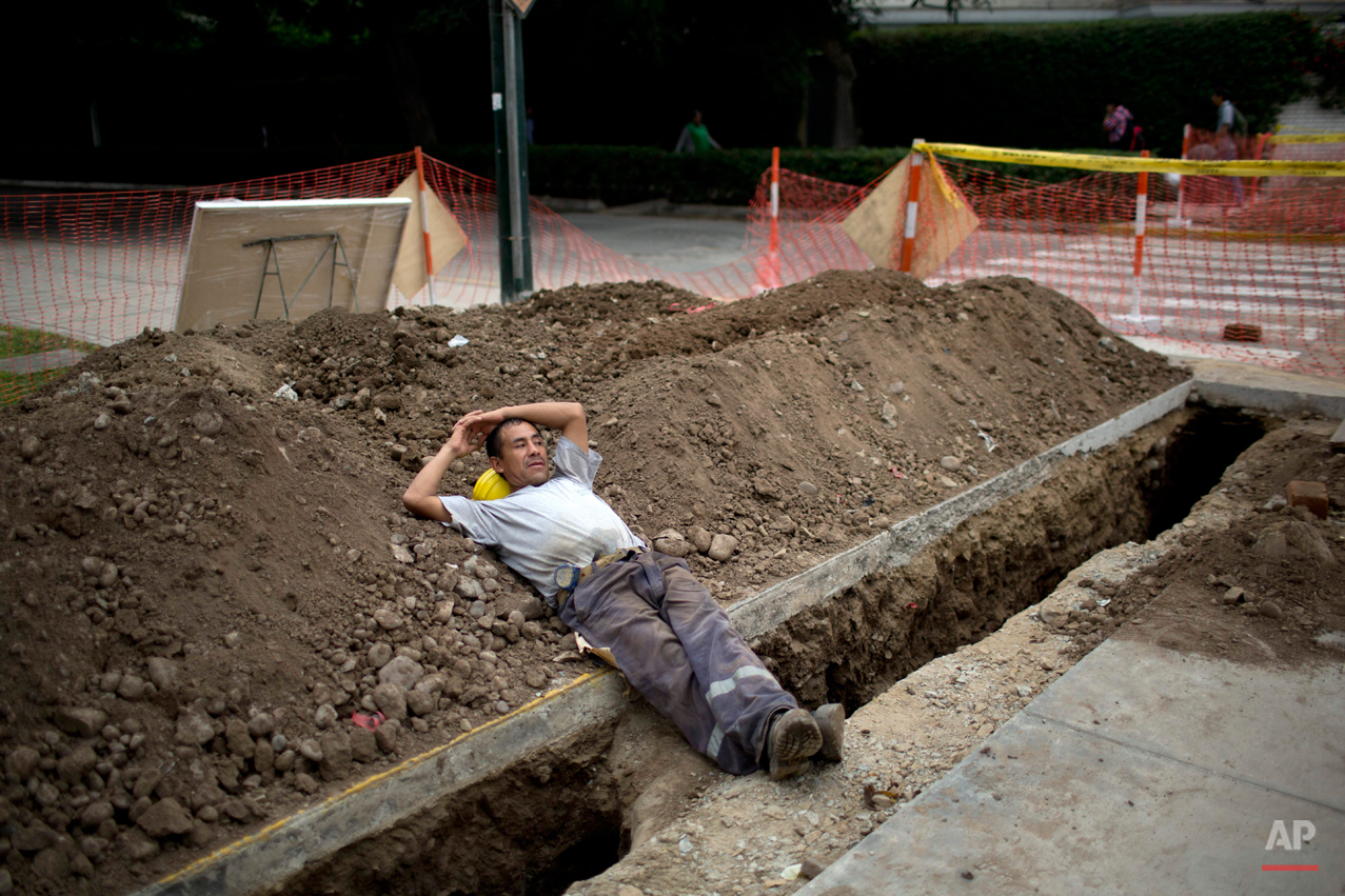 German Palencia rests on a pile of dirt after digging ditches for a telecommunications company in Lima Peru, Friday, June 6, 2014.  (AP Photo/Rodrigo Abd)