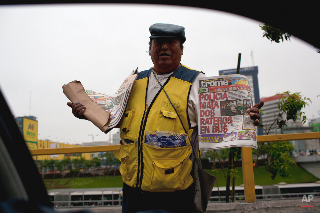 "A newspaper vendor shows the cover of a newspaper with the headline in Spanish ""Police kill two petty thieves inside a bus"" in Lima, Peru, Monday, Nov. 5, 2012. (AP Photo/Rodrigo Abd)"