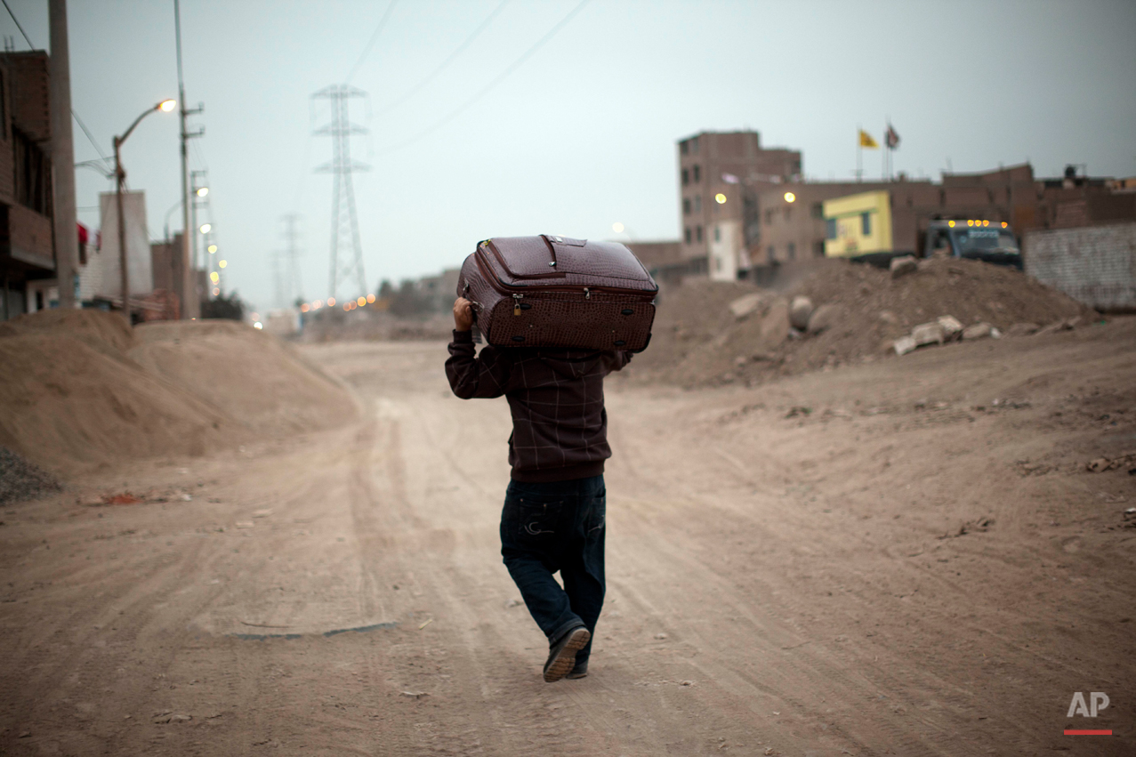 A man hauls a suitcase on along a dirt road in the Santa Rosa Chuquitanta neighborhood in Lima, Peru, Thursday, July 25, 2013. (AP Photo/Rodrigo Abd)
