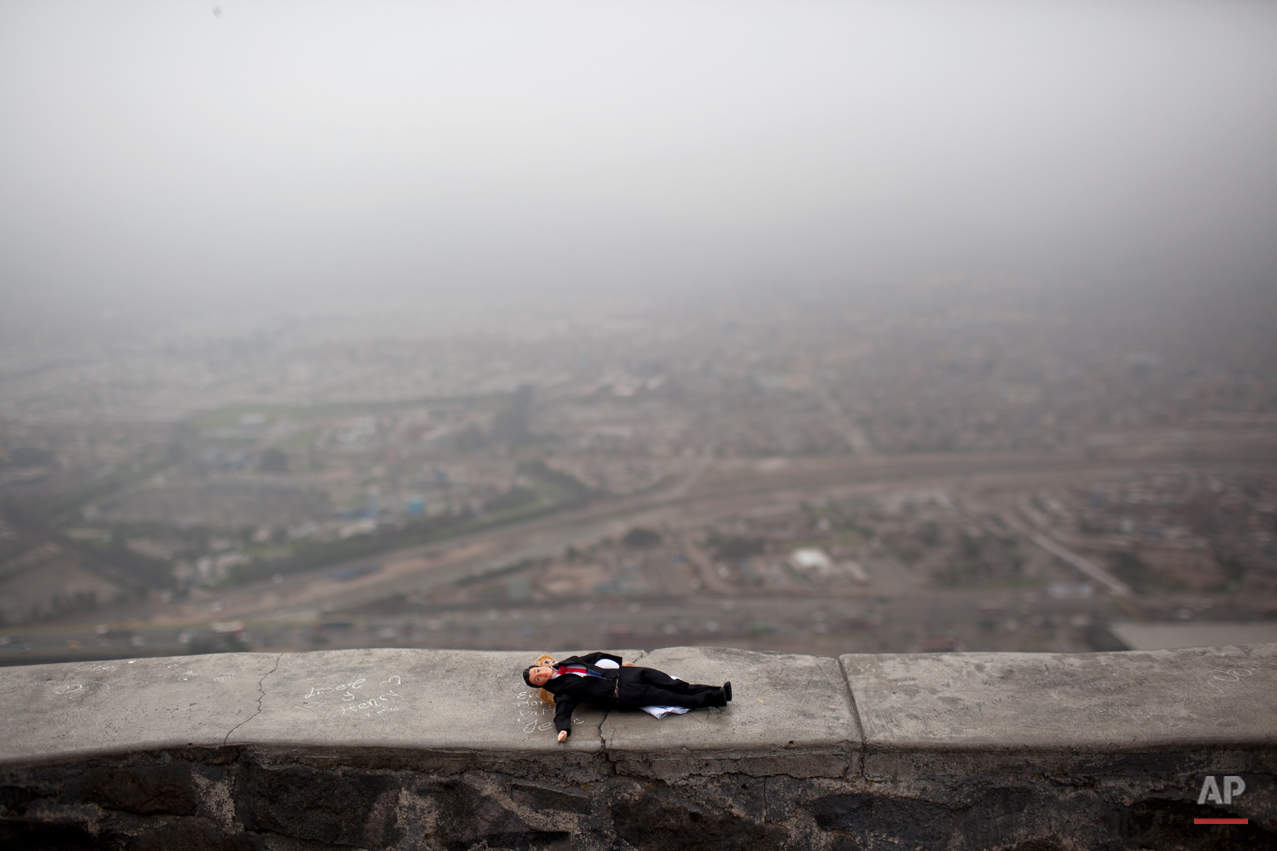 A doll left momentarily by a girl who was playing with it lays on the wall the lookout point from Cerro San Cristobal, Lima, Peru, Monday, Nov. 5, 2012. (AP Photo/Rodrigo Abd)