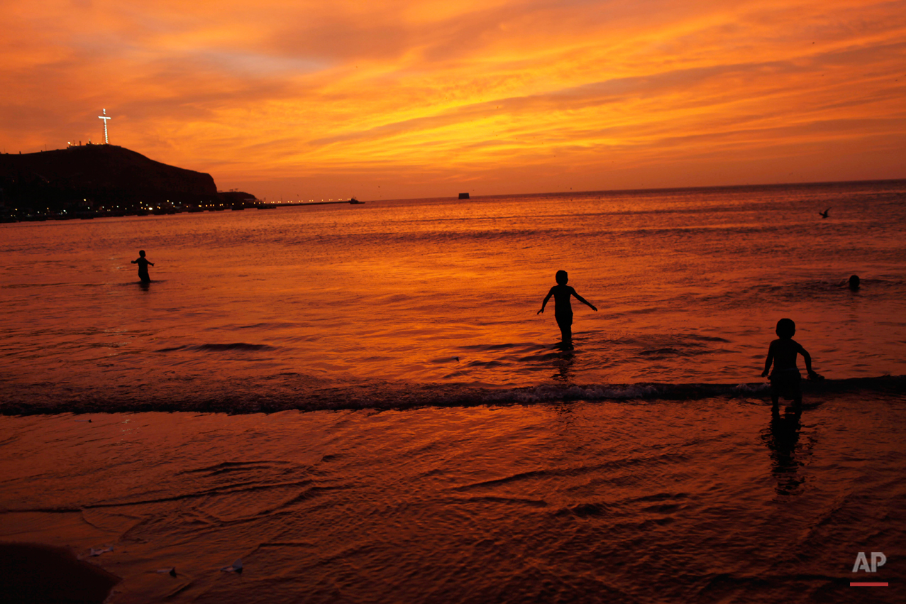 Children play on the shore of the Pacific Ocean in Lima, Peru, Sunday, Jan. 13, 2013. (AP Photo/Rodrigo Abd)