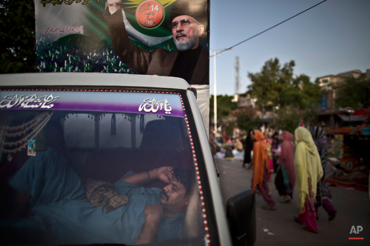 A supporter of anti-government cleric Tahir-ul-Qadri, sleeps inside a vehicle decorated with a big poster showing Tahir-ul-Qadri, during a protest, in Islamabad, Pakistan, Sunday, Aug. 17, 2014. Qadri led massive rallies Saturday in Pakistanís capital, demanding Prime Minister Nawaz Sharif step down over alleged fraud in last yearís election in front of thousands of protesters. (AP Photo/Muhammed Muheisen)