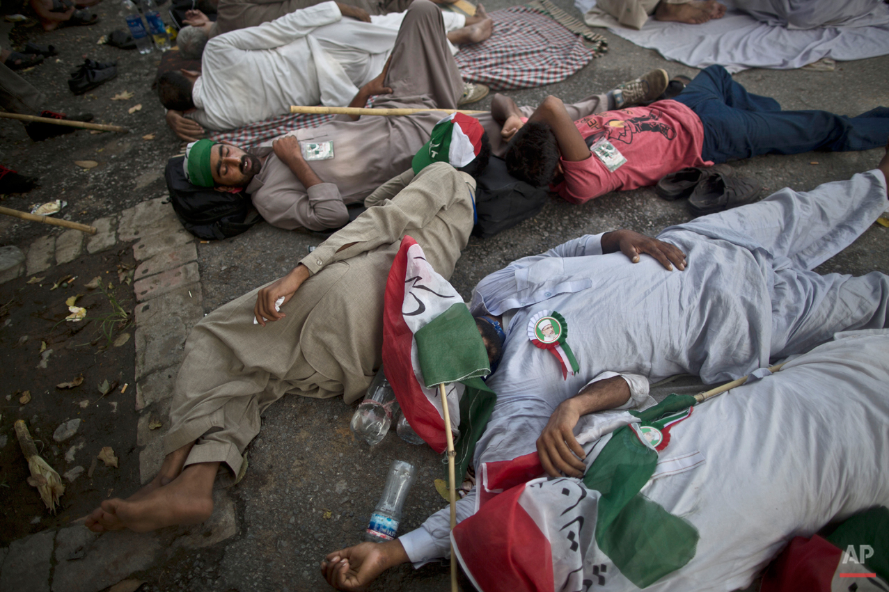 Supporters of fiery anti-government cleric Tahir-ul-Qadri, wearing pins showing his image, sleep on the ground, after marching all night long from Lahore to Islamabad, at the site of a rally in Islamabad, Pakistan, Saturday, Aug. 16, 2014. Qadri led massive rallies Saturday in Pakistanís capital, demanding Prime Minister Nawaz Sharif step down over alleged fraud in last yearís election in front of thousands of protesters. (AP Photo/Muhammed Muheisen)