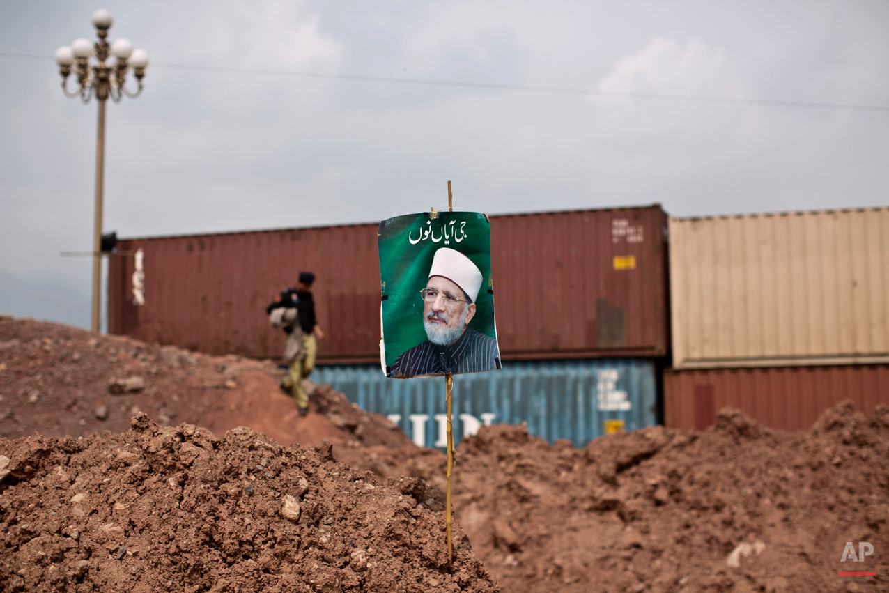 """A poster showing anti-government cleric Tahir-ul-Qadri, is left by his supporters in a barricade near the Parliament building, in Islamabad, Pakistan, Thursday, Aug. 21, 2014. Pakistani officials held """"initial"""" talks before dawn Thursday with representatives from two opposition groups whose supporters have been besieging the parliament for a second day demanding the prime minister resign over alleged election fraud, the government said. (AP Photo/Muhammed Muheisen)"""