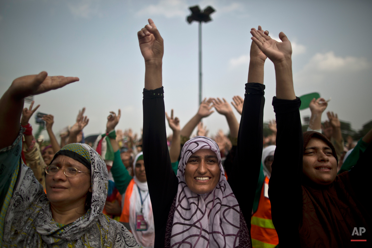 """Female supporters of anti-government cleric Tahir-ul-Qadri react to his speech during a protest in front of the Parliament building, in Islamabad, Pakistan, Thursday, Aug. 21, 2014. Pakistani officials held """"initial"""" talks before dawn Thursday with representatives from two opposition groups whose supporters have been besieging the parliament for a second day demanding the prime minister resign over alleged election fraud, the government said. (AP Photo/Muhammed Muheisen)"""