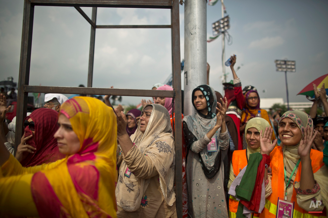 """Female supporters of anti-government cleric Tahir-ul-Qadri listen to his speech, during a protest in front of the Parliament building, in Islamabad, Pakistan, Thursday, Aug. 21, 2014. Pakistani officials held """"initial"""" talks before dawn Thursday with representatives from two opposition groups whose supporters have been besieging the parliament for a second day demanding the prime minister resign over alleged election fraud, the government said. (AP Photo/Muhammed Muheisen)"""