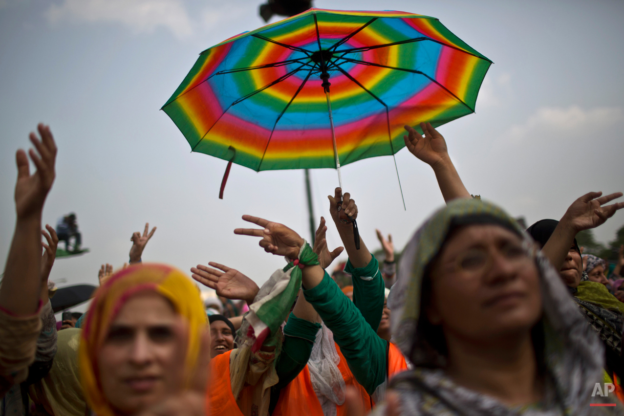 """Female supporters of anti-government cleric Tahir-ul-Qadri react after his speech during a protest in front of the Parliament building, in Islamabad, Pakistan, Thursday, Aug. 21, 2014. Pakistani officials held """"initial"""" talks before dawn Thursday with representatives from two opposition groups whose supporters have been besieging the parliament for a second day demanding the prime minister resign over alleged election fraud, the government said. (AP Photo/Muhammed Muheisen)"""