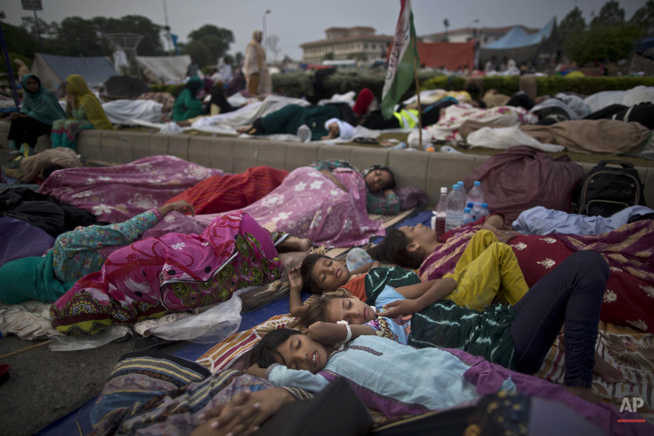 Pakistani children and female protestors sleep in front of the parliament building, during weeklong protests from the eastern city of Lahore to the gates of parliament calling for Prime Minister Nawaz Sharif's ouster over alleged voting fraud, in Islamabad, Pakistan, Friday, Aug. 22, 2014. They swarmed into the capital in their thousands, protesters calling for the prime minister's resignation and the dissolution of parliament. The week-long protests in the capital and around the parliament building have been loud and boisterous but peaceful. But despite their color, there is the other side to the demonstrations _ the increased demand for food, water and toilets to accommodate the thousands of people who turned out to support cricketer-turned-politician Imran Khan and popular cleric Tahir-ul-Qadri. (AP Photo/Muhammed Muheisen)