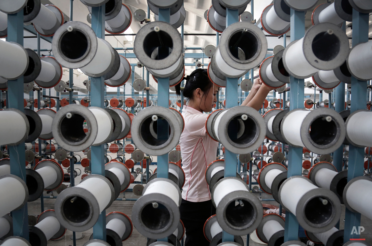 A North Korean woman works at the Kim Jong Suk Pyongyang textile factory, Thursday, July 31, 2014, in Pyongyang, North Korea. This is the country's largest textile factory with 8,500 workers, where eighty percent of them are women.  (AP Photo/Wong Maye-E)