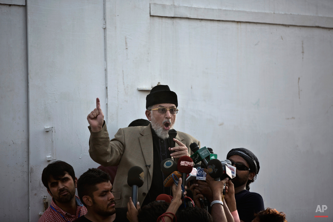 Anti-government cleric Tahir-ul-Qadri, gestures while delivering a speech to his supporters, during a protest in front of the Parliament building in Islamabad, Pakistan, Wednesday, Aug. 20, 2014. (AP Photo/Muhammed Muheisen)