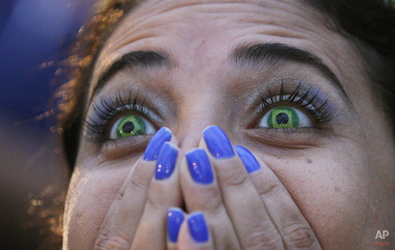 A Brazil soccer fan wearing contact lenses that mimic the Brazilian flag watches her team lose to Germany in a World Cup semifinal game via live telecast inside the FIFA Fan Fest area on Copacabana beach in Rio de Janeiro, Brazil, Tuesday, July 8, 2014. (AP Photo/Leo Correa)
