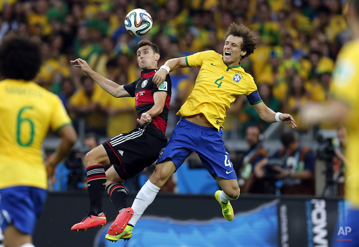 Germany's Miroslav Klose, left, and Brazil's David Luiz go for a header during the World Cup semifinal soccer match between Brazil and Germany at the Mineirao Stadium in Belo Horizonte, Brazil, Tuesday, July 8, 2014. (AP Photo/Frank Augstein)