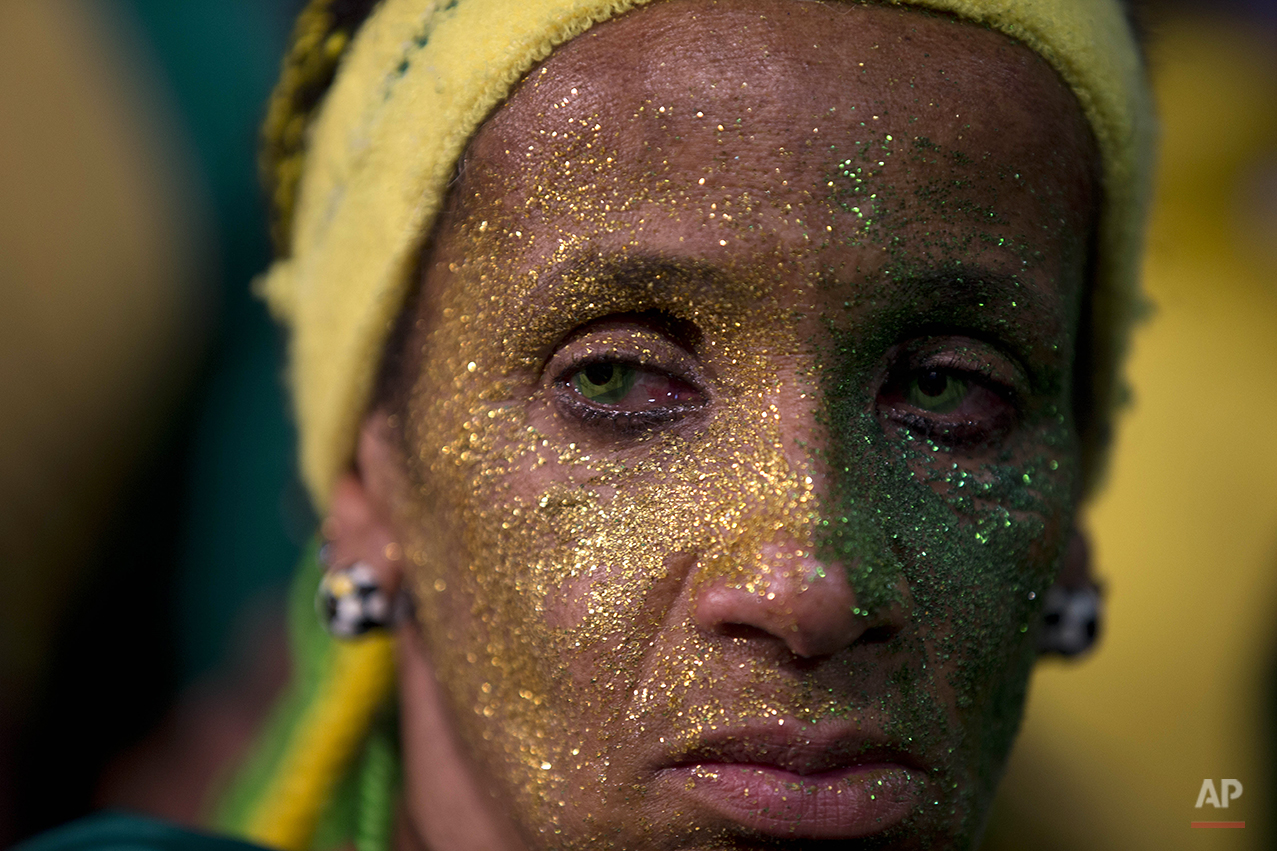 A fan of the Brazilian national soccer team looks on as her team loses to Germany in a semi-final match at the FIFA Fan Fest during the 2014 soccer World Cup, in Sao Paulo, Brazil, Tuesday, July 8, 2014. (AP Photo/Dario Lopez-Mills)