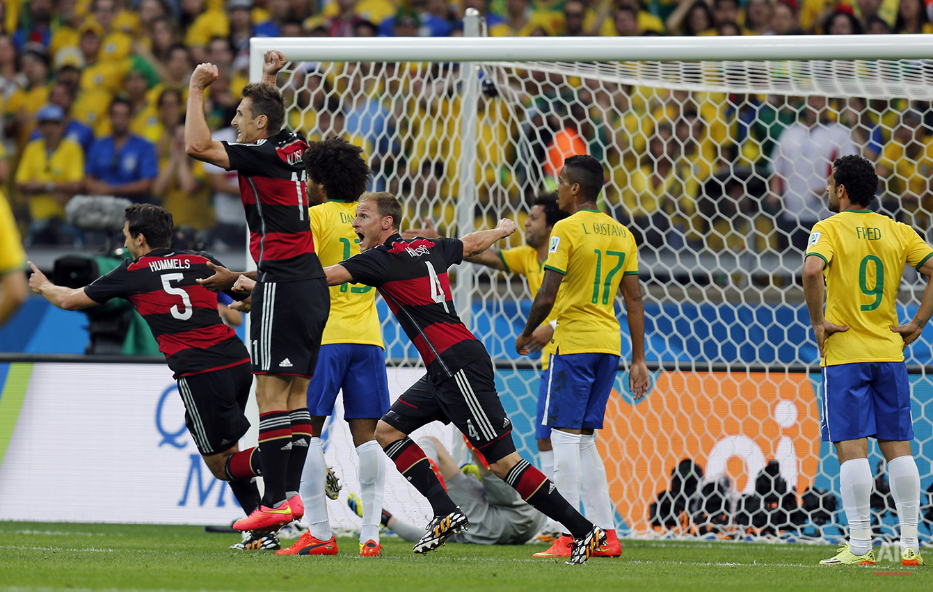 Germany's Mats Hummels, Miroslav Klose and Benedikt Hoewedes, from left, celebrate after their teammate Thomas Mueller scored the opening goal during the World Cup semifinal soccer match between Brazil and Germany at the Mineirao Stadium in Belo Horizonte, Brazil, Tuesday, July 8, 2014. (AP Photo/Frank Augstein)