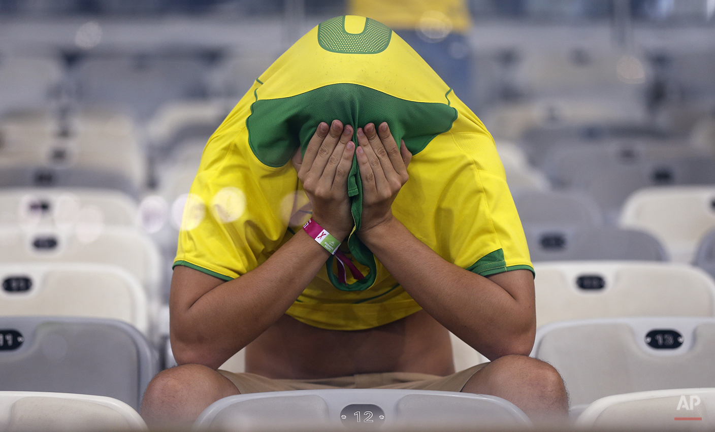 A Brazil fan covers his face after the World Cup semifinal soccer match between Brazil and Germany at the Mineirao Stadium in Belo Horizonte, Brazil, Tuesday, July 8, 2014. Germany beat Brazil 7-1 and advanced to the final.  (AP Photo/Frank Augstein)