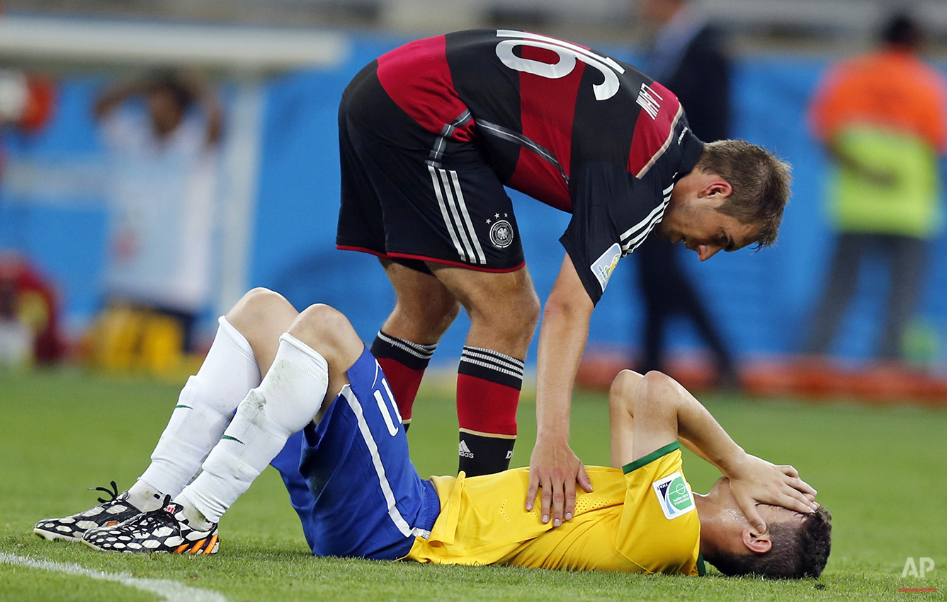 Brazil's Oscar, bottom, is comforted by Germany's Philipp Lahm during the World Cup semifinal soccer match between Brazil and Germany at the Mineirao Stadium in Belo Horizonte, Brazil, Tuesday, July 8, 2014. Germany beat Brazil 7-1 and advanced to the final. (AP Photo/Frank Augstein)