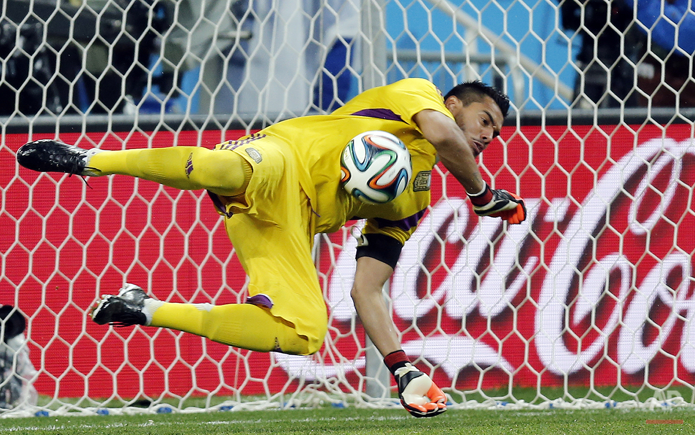 Argentina's goalkeeper Sergio Romero saves a shot from the penalty spot by Netherlands' Ron Vlaar in the shoot-out of the World Cup semifinal soccer match between the Netherlands and Argentina at the Itaquerao Stadium in Sao Paulo, Brazil, Wednesday, July 9, 2014. (AP Photo/Frank Augstein)