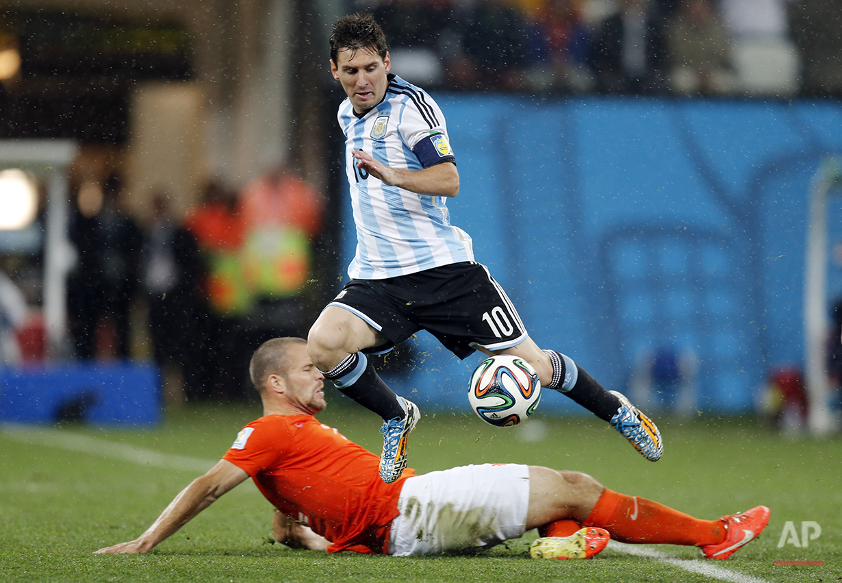 Netherlands' Ron Vlaar, bottom, tackles Argentina's Lionel Messi during the World Cup semifinal soccer match between the Netherlands and Argentina at the Itaquerao Stadium in Sao Paulo, Brazil, Wednesday, July 9, 2014. (AP Photo/Frank Augstein)