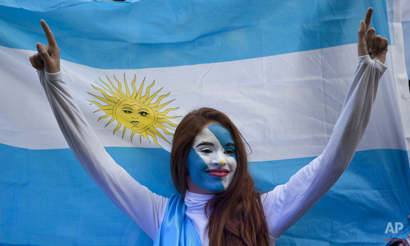 An Argentina soccer fan poses in front of an Argentine flag before a World Cup semifinal match between Argentina against Netherlands, on a street where an outdoor screen has been set for viewing, in Buenos Aires, Argentina, Wednesday, July 9, 2014. (AP Photo/Eduardo Di Baia)