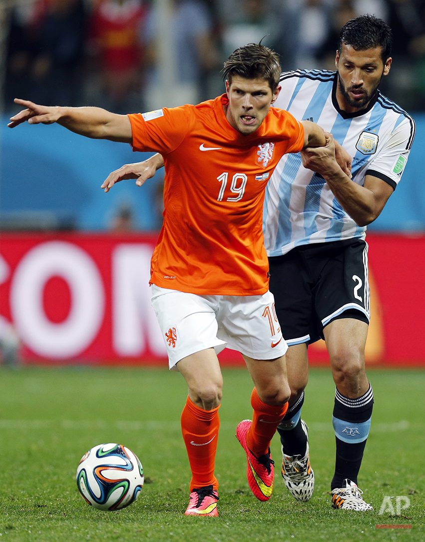 Netherlands' Klaas-Jan Huntelaar, left, is held by Argentina's Ezequiel Garay during the World Cup semifinal soccer match between the Netherlands and Argentina at the Itaquerao Stadium in Sao Paulo, Brazil, Wednesday, July 9, 2014. (AP Photo/Frank Augstein)