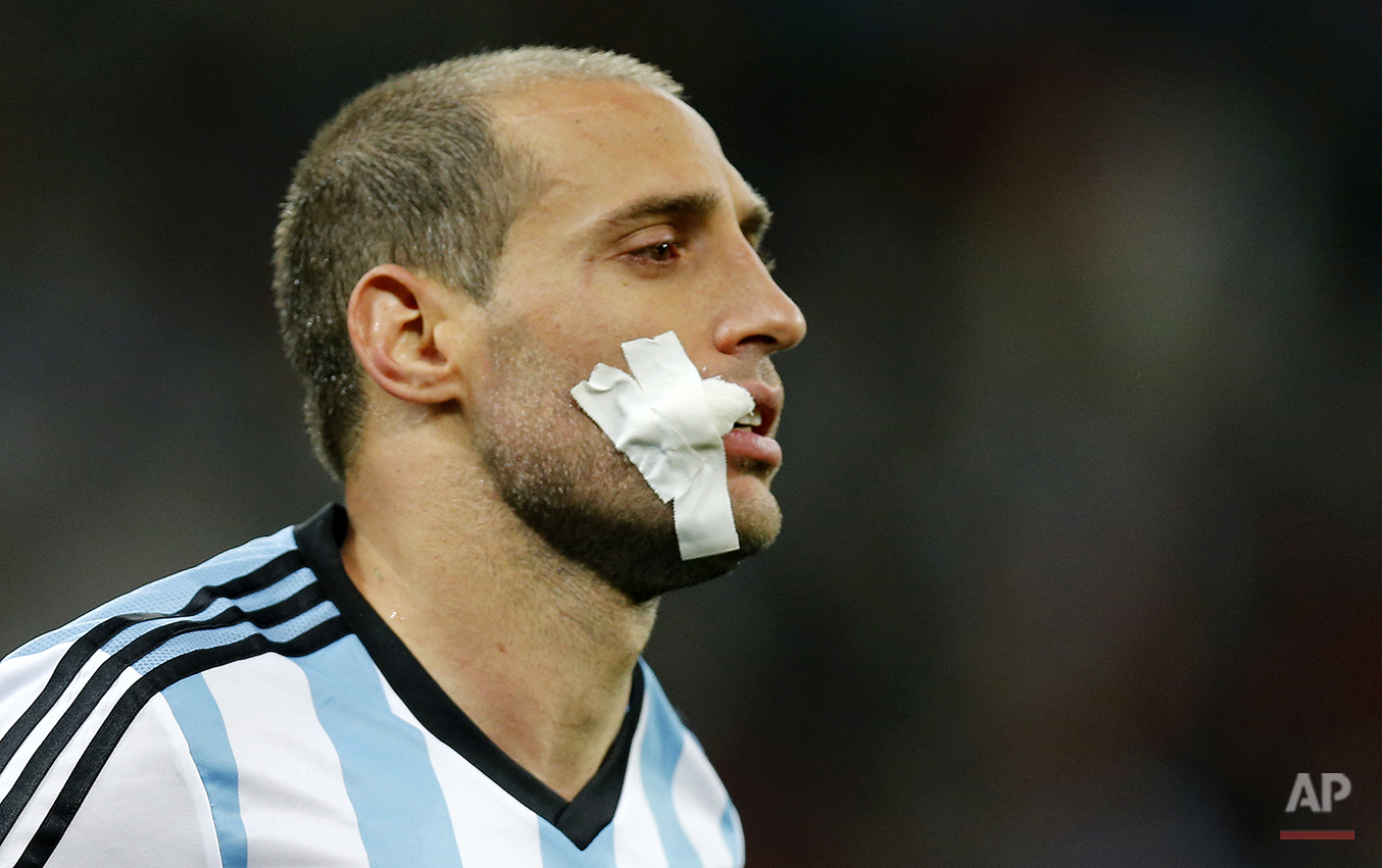 Argentina's Pablo Zabaleta has his face covered with gauze during the World Cup semifinal soccer match between the Netherlands and Argentina at the Itaquerao Stadium in Sao Paulo, Brazil, Wednesday, July 9, 2014. (AP Photo/Frank Augstein)