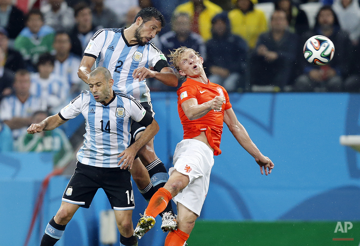 Netherlands' Dirk Kuyt, right, goes for a header with Argentina's Javier Mascherano, left, and Ezequiel Garay during the World Cup semifinal soccer match between the Netherlands and Argentina at the Itaquerao Stadium in Sao Paulo, Brazil, Wednesday, July 9, 2014. (AP Photo/Frank Augstein)